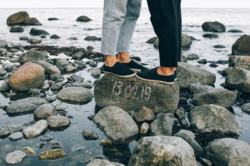 A close up of newlyweds standing on a rock at a beach in Mons Klint with their LGBT wedding date written on it.