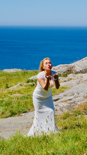 a bride sending air kiss in the front of the sea