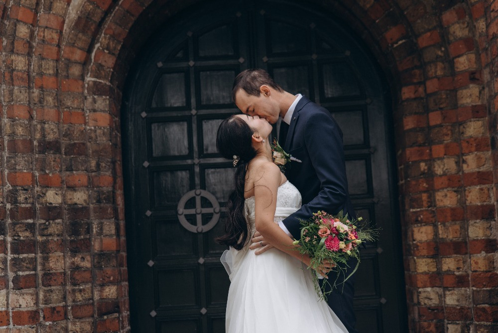 Amazing couple kissing passionately in the front of Danish Church right after their Danish marriage