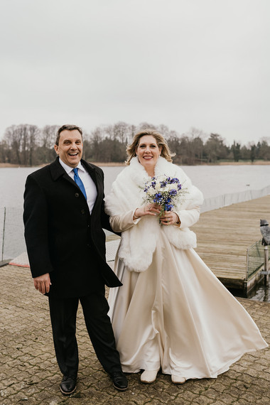 A couple smiling during their winter wedding at Lolland Island after booking our wedding package abroad for two to Denmark