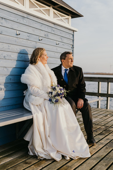 A bride and groom sitting by a wooden cottage on the waterfront during their winter wedding in Denmark