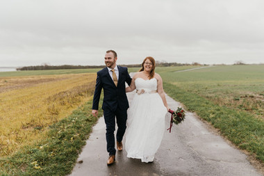 Newlyweds walking through the beautiful Lolland Island as a part of their adventure elopement to Denmark