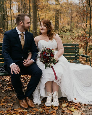 A couple sitting on a bench in the middle of a forest happy during their elopement in Denmark.