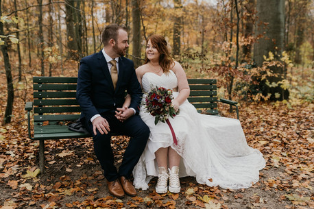 a-bride-couple-sit-on-a-bench