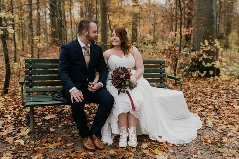 Newlyweds sitting on a bench in the middle of a forest while on getting married in Denma