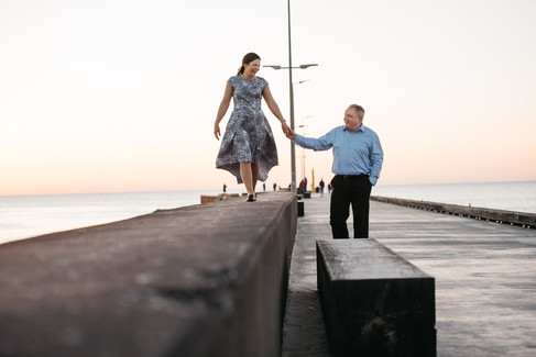 A couple walking down the pier hand-in-hand after they renew wedding vows in a charming town.