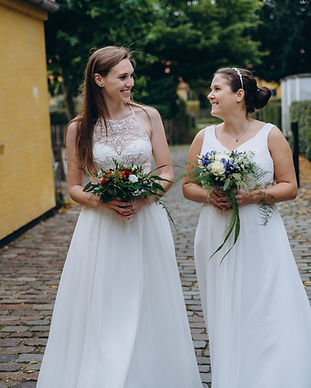 A lesbian couple holding their bouquets and smiling as they have fun during their same sex wedding in Denmark.