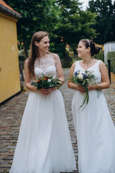 Two brides smiling and looking at each other as they enjoy their same-sex wedding in Denmark on Lolland Island