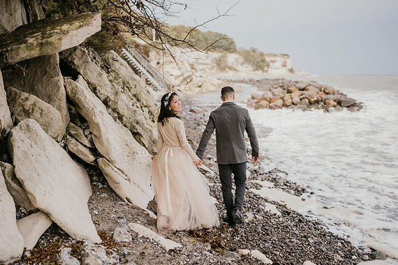 A groom and his bride enjoying their elopement ceremony abroad in Denmark while exploring Stevens Klint.
