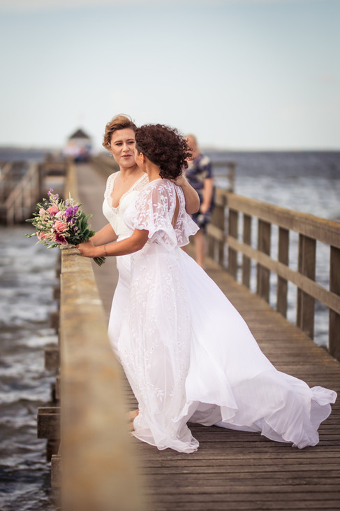 Newlyweds enjoying their gay marriage in Denmark as they stand on the pier by the beach where they had their same-sex wedding ceremony.