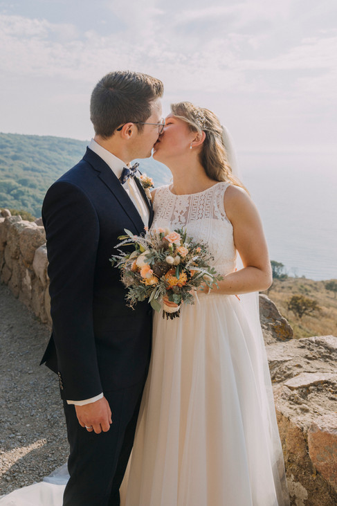 Newlyweds kissing at the Hammershus Ruins on Bornholm Island during their island wedding adventure elopement in Denmark.