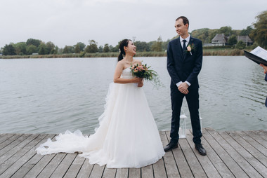 A bride getting emotional while her groom reads wedding vows during their adventure elopement in Denmark as they elope abroad to get married.