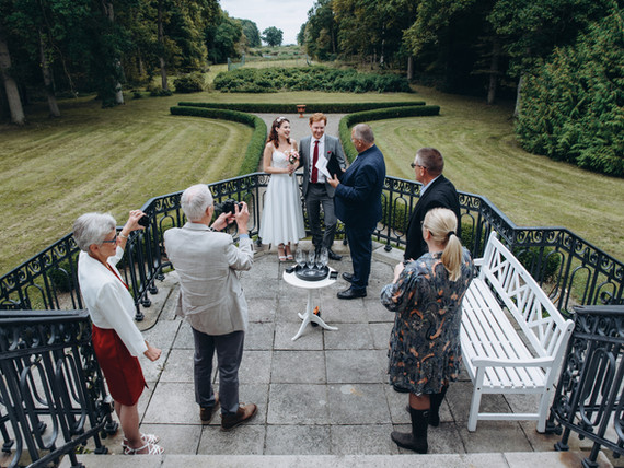 A small castle wedding being held at the Vindeholme courtyard, a couple saynig their vows during their wedding island adventure.