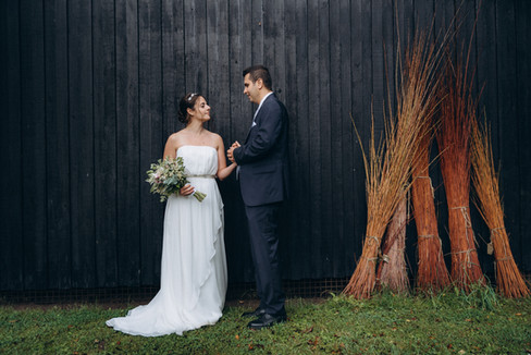 A couple standing by the barn of an open-air museum, one of the most romantic wedding venues if you are interested in getting married in Denmark.