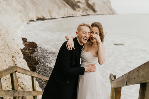 Husband and wife laughing and hugging by Mons Klint during their winter island adventure made possible by our Denmark elopement packages for intimate weddings abroad.