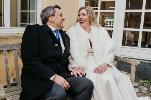 Newlyweds sitting on a bench in Maribo during their winter wedding in Denmark in Lolland Island.