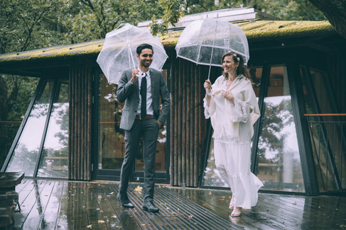 A couple laughing and having fun with their umbrellas outside their all-inclusive treehouse, a great marry abroad idea for forest elopement weddings in Denmark.