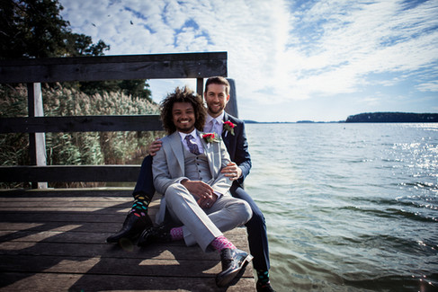 A couple holding each other and sitting by the Maribo Lake during their elopement in Denmark during their same-sex wedding adventure.