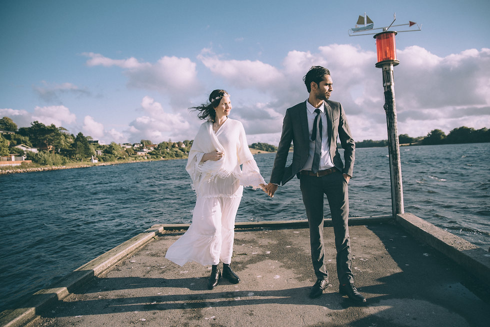 A couple by the sea during their small wedding abroad in Denmark.