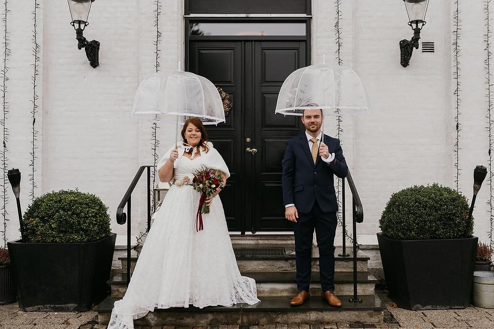 Bride-and-groom-stands-undertransparent-umbrellas