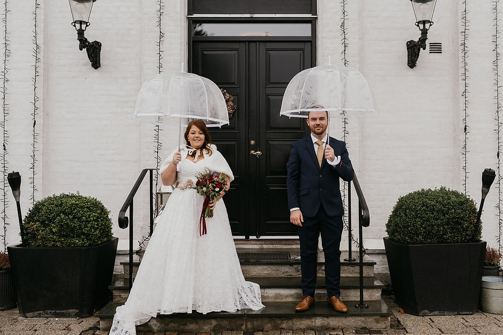 Newlyweds holding their umbrellas and smiling during their adventure elopement in Denmark