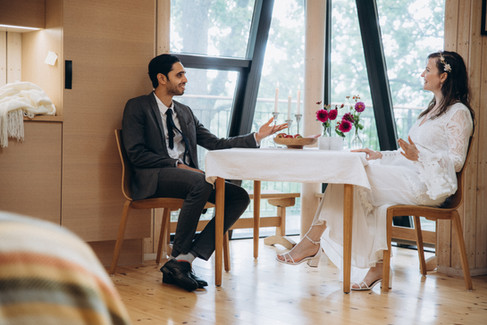 Newlyweds having an intimate dinner inside their treehouse, an all-inclusive Denmark elopement package offered by Nordic Adventure Weddings.