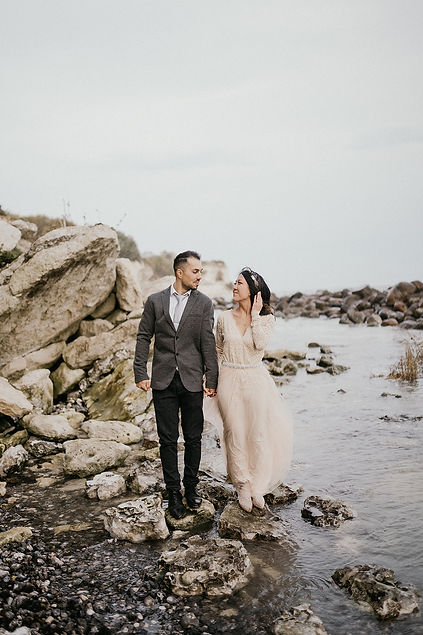 A bride and groom posing on the rocks as they have chosen elopement package abroad for two.