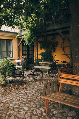 A cute part of Stege, with colorful yellow walls, trees, benches, and a bicycle, one of the many charming sights you will see during your adventure elopement to Møn Island