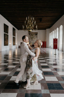 A couple dancing within the historical halls of Elsinore castle during their Danish island wedding experience