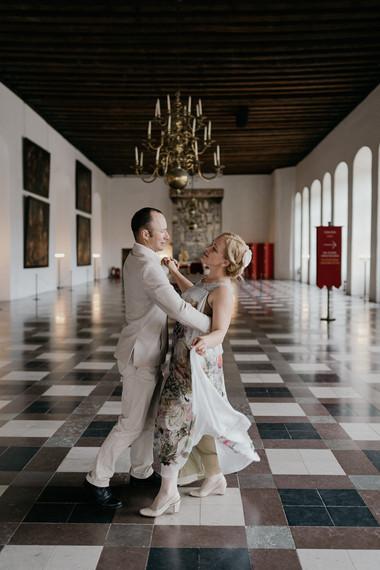 Newlyweds dancing inside of Hamlet's Elsinore Castle as they enjoy their island wedding In Denmark