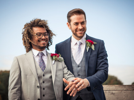 A couple holding hands and smiling during their same-sex marriage in Denmark for foreigners.