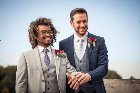 Two grooms smiling and showing their wedding bands while getting married in Denmark, one of the best places to get married abroad for gay couples.