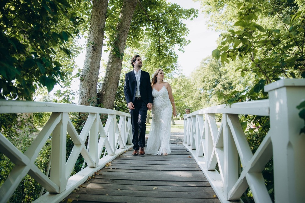 A couple walking on the bridge in rose garden, a perfect  venue for your wedding in Denmark