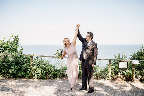 A couple holding up their hands in celebration during their elopement in Denmark  at Stevens Klint, one of our most popular wedding packages abroad for two.