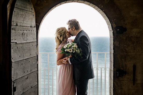 Newlyweds kissing under the church arch on Stevens Klint while getting married in Denmark during their adventure elopement abroad.