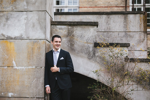 A groom smiling in front of a castle facade as he gets married in Denmark.