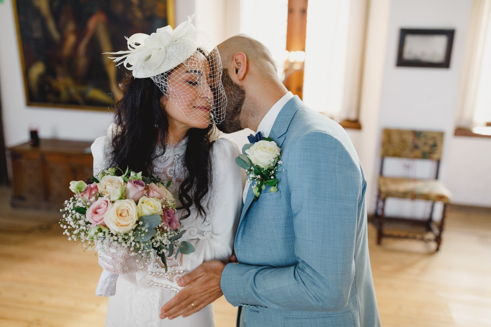 A poertrait of a happy couple at their castle wedding ceremony with colorful bridal bouquet from roses.
