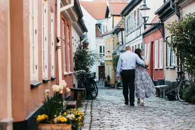 A couple walking through Lokken's colorful streets, a great vow renewal idea for couples wanting to intimately celebrate their love abroad.
