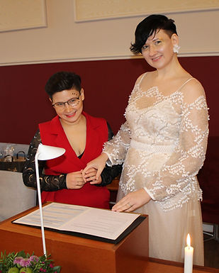 Two brides rejoicing during their wedding abroad, happy about Denmark's same-sex marriage laws.
