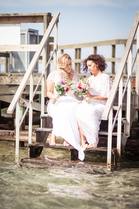 Newlyweds sitting on the pier during their bohemian wedding in Denmark, a perfect same-sex wedding idea for elopements abroad.
