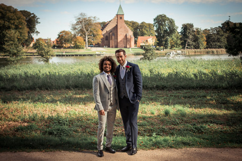 A gay couple standing by the Maribo Lake and smiling with the Great Cathedral in the background during their gay marriage in Denmark.