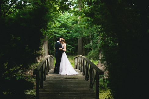 A husband hugging his wife at the wooden bridge in a park during their castle wedding adventure in Denmark.