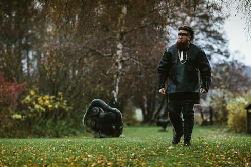 A man walking through a Nordic field approaching his Denmark wedding venue