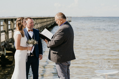 An outdoor beach wedding by the Hestehoved Jetty in Lolland Island, one of the best places to get married abroad in Denmark