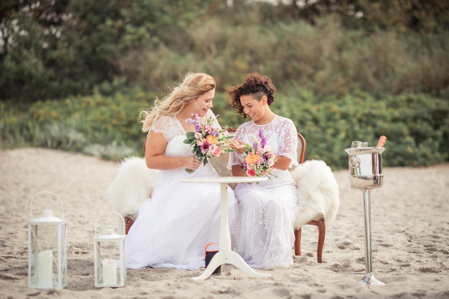 A same-sex couple signing paperwork outdoros on the beach and enjoying their island marriage abroad and to their Denmark destination elopement on the beach.