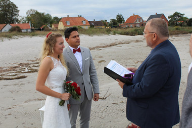 a couple listening to the oaths they will take on their beach wedding in Denmark.elopement in Denmark.