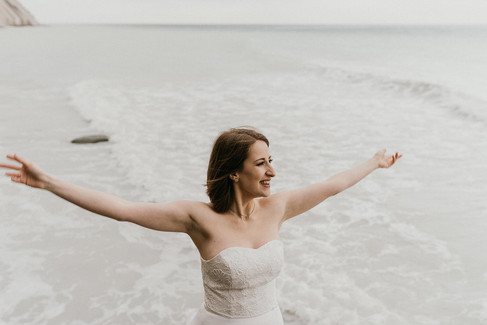 A bride opening up her hands in joy as she celebrates her adventure wedding in Denmark