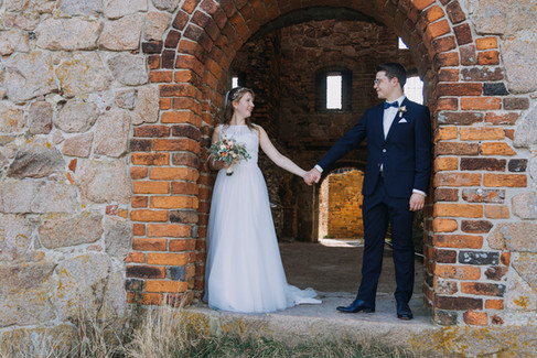 Newlyweds holding hands and looking into each other's eyes during their wedding abroad in Denmark, enjoying their Danish wedding at the Hammershus Ruins on Bornholm Island.