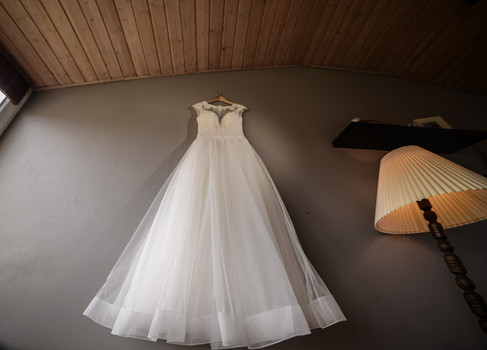 A picture of a bride's dress hanging on the wall as the preparations go on of a Nordic wedding abroad in Denmark.