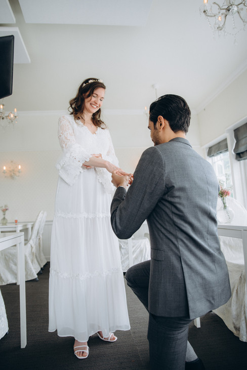 A groom putting on a wedding band on his wife's finger while getting married in Denmark